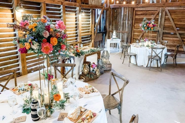 Why Microweddings in Central PA are Trending. Intimate seating at circular tables with floral pink and orange arrangements
